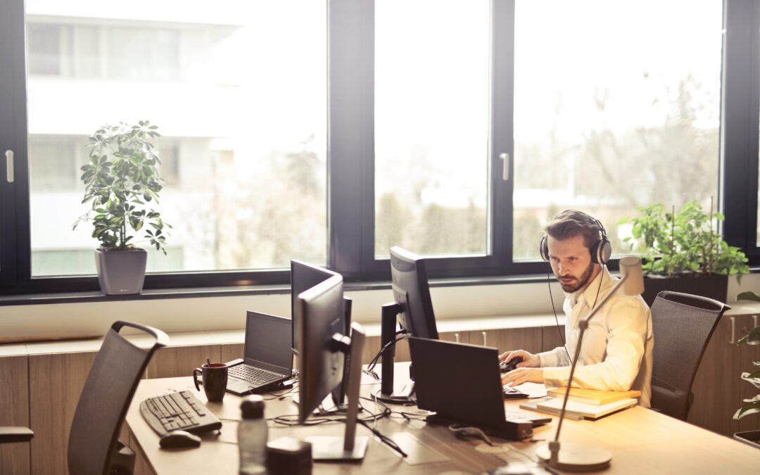 man with headphones facing computer monitor 845451 1 scaled